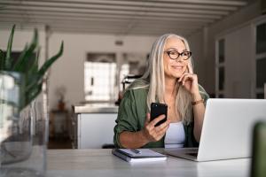 Frau mit Handy vor Laptop