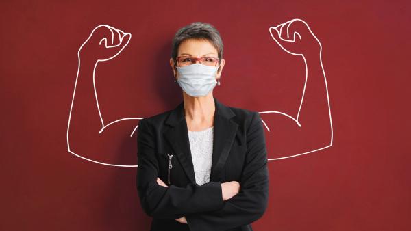 Seniorin vor einer roten Wand mit Mund-Nasen-Schutz