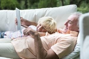 Großvater und Enkel schauen in einen E-Book-Reader