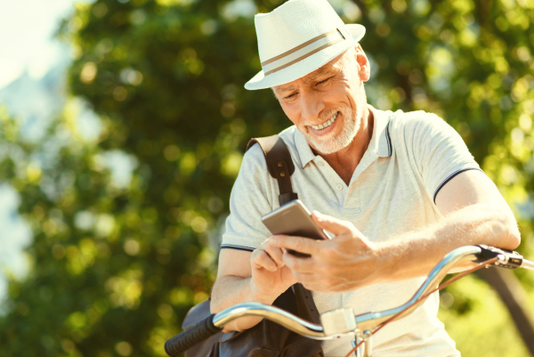 Senior beim Radfahren mit Smartphone
