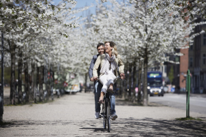 Paar radelt durch die Stadt zwischen blühenden Bäumen