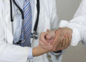 Arzt untersucht Frauenhand