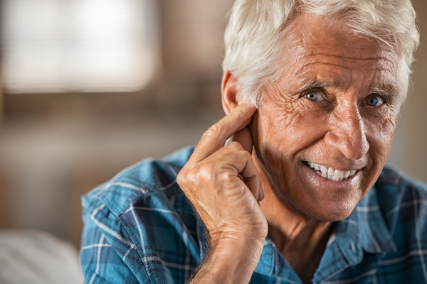 Älterer Mann, der sich das Ohr hält