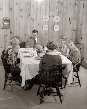 Schwarz-Weiß-Foto einer Familie in den 50er Jahren beim Tischgebet