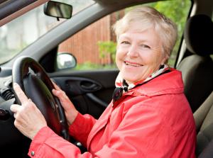 Seniorin in roter Jacke am Steuer eines Autos