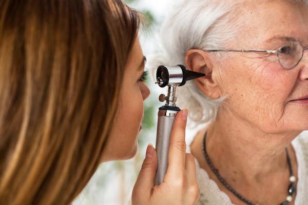 HNO-Ärztin, die einer Rentnerin ins Ohr schaut