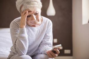 Frau schaut traurig auf das Smartphone