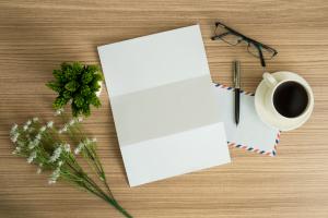 Briefpapier, Blumen, Brille auf einem Tisch