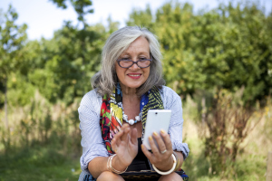 In ein Handy blickende Seniorin im Grünen