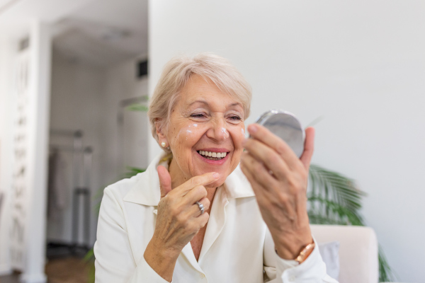 Seniorin beim Eincremen des Gesichts