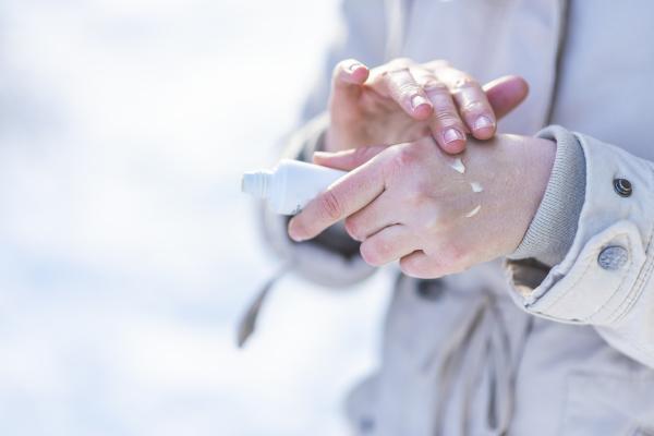Frau cremt Hände ein