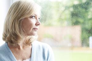 Frau schaut traurig aus dem Fenster