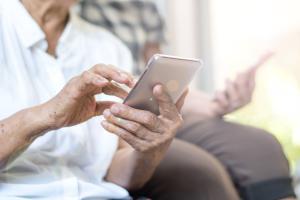 Seniorenpaar mit Handys auf dem Sofa