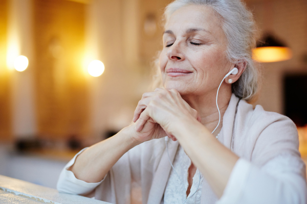 Seniorin hört Musik über Kopfhörer
