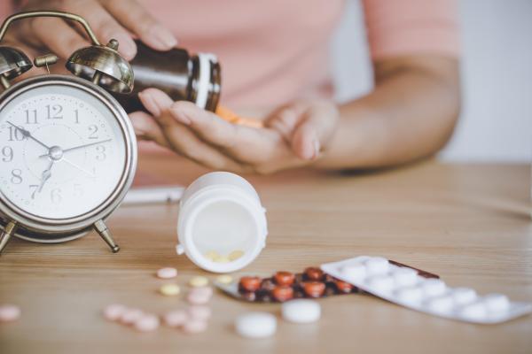 Frau vor verschiedenen Tabletten und Wecker auf einem Tisch