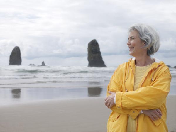 Frau mit gelber Jacke am Strand