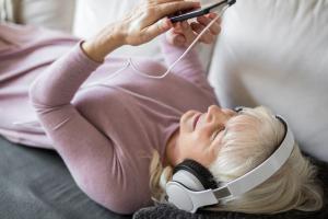 Frau mit Kopfhörern und Handy