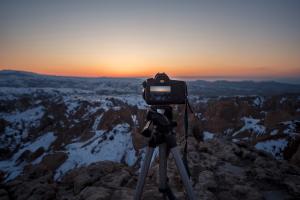 Kamera auf einem Stativ vor einer Berglandschaft