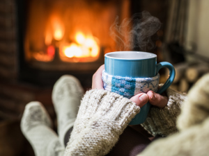 mit dicken Socken und Tee vor dem Kaminfeuer