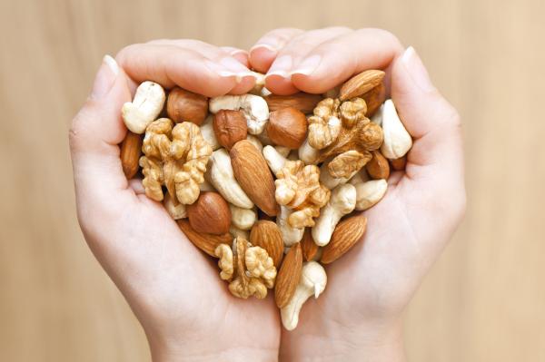 Nüsse in Frauenhand die ein Herz formt