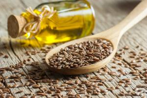 Leinsamen in Holzlöffel und Leinöl