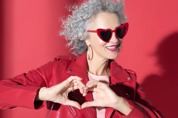 Grauhaarige Frau im roten Mantel vor roter Wand