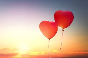 Zwei Herzluftballons vor dem blauen Himmel