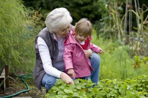 ältere Frau mit kleinem Mädchen im Garten