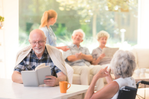 mehrere Senioren und eine Pflegerin in einem hellen Raum