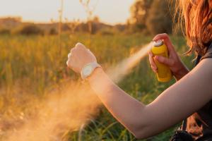 Frau sprüht Insektenschutzspray auf den Arm