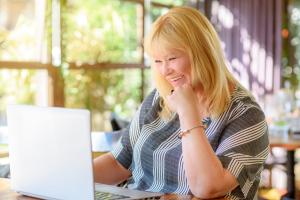 Seniorin vor Laptop beim Chatten