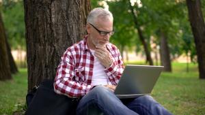 Mann mit Laptop sitzt angelehnt an einen Baum