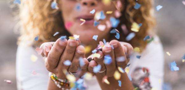 Frau mit Konfetti auf geöffneter Hand