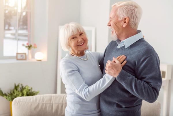 Glückliches Seniorenpaar, das zuhause tanzt