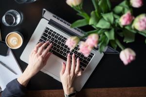 Frauenhand auf Laptop-Tastatur