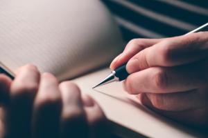 Frauenhand schreibt in Kladde