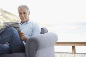 Senior sitzt mit gekreuzten Beinen auf Terrasse und liest
