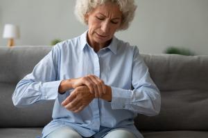 Seniorin massiert Handgelenk