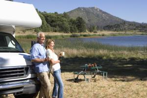 Seniorenpaar lehnt an Camper an einem See