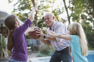 Senior spielt Ball mit Enkeln