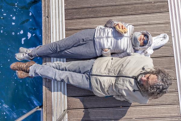 Älteres Paar auf Bootssteg in der Wintersonne