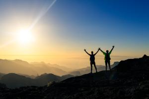 zwei Personen auf dem Gipfel eines Berges