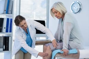 Ärztin untersucht Knie
