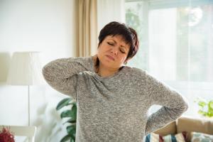 Frau greift sich an den schmerzenden Rücken