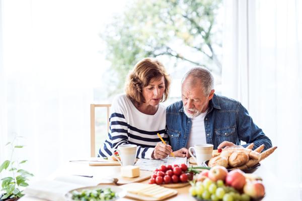 Älteres Ehepaar beim Frühstücken und Rätseln