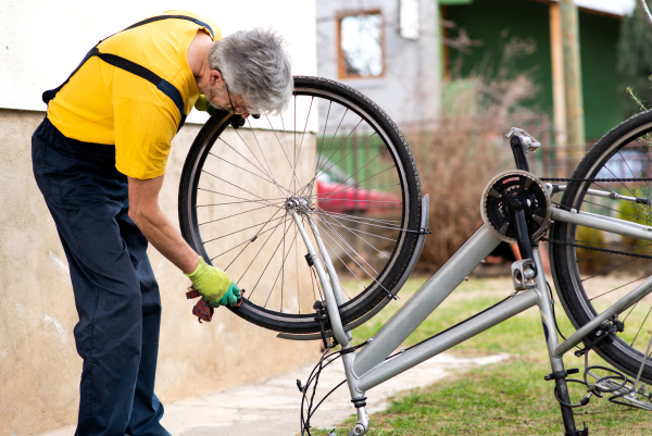 Senior beim Putzen seines Rads