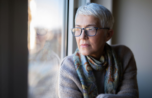 Seniorin schaut traurig aus einem Fenster