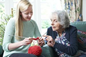 Seniorin und Enkelin beim Stricken