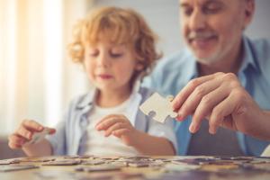 Senior und Enkel puzzeln
