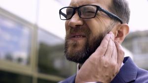 Geschäftsmann mit Ohrenjucken